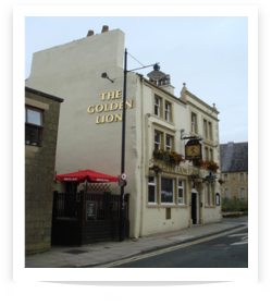 Picture of The Golden Lion Pub taken from the side showing golden plated letters forming the name of the pub